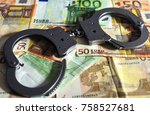 handcuffs on a pile of euro... | Shutterstock . vector #758527681