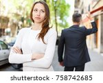 Small photo of Offended girl on departing boyfriend background after quarrel outdoors