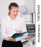 Small photo of Woman is signing agreement papers of financial nature at office.