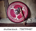 Stock photo a viking axe leans against a circular shield with a celtic tree pattern on it 758799487