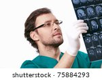 Surgeon gloves considering X-rays on a white background - stock photo