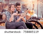 young loving couple sitting on... | Shutterstock . vector #758885119