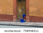 Small photo of Woman in Blue-a woman sitting in a doorway with old wooden double doors and a colorful old wall, covered in a long blue shawl, in San Migule de Allende, Mexico