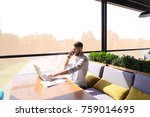 Small photo of Responsible estate agent browsing with laptop and calling by smartphone to girlfriend at workplace. Young purposeful man dressed in white shirt has dark hair and beard. Concept of advantageous new