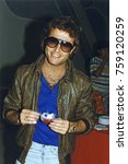 Small photo of Burbank, California - exact date unknown - circa 1987 - the late Andy Gibb attending a party and holding a cup of punch