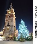 Giant christmas tree illuminated at night standing next to historical Town Hall tower on the Main Market Square in Krakow - stock photo
