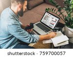 man sits at table working holds ... | Shutterstock . vector #759700057