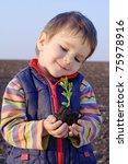 Little Boy On Field Holding Th...