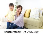 mother tieing child's hair... | Shutterstock . vector #759932659