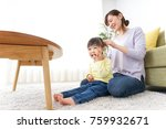 mother tieing child's hair... | Shutterstock . vector #759932671