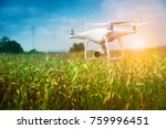 Drone flying above the corn field for survey the crop and wind turbine background - stock photo
