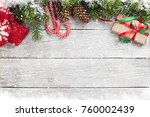 Small photo of Christmas gift box, candy cane, mittens and snow fir tree on wooden table. Top view with space for your greetings