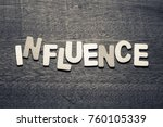 Small photo of Influence word by wood letters on wood background