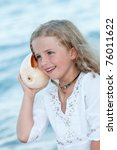 Summer vacation - Listening to the sea - beautiful girl with shell at the beach - stock photo