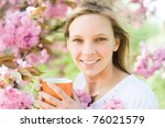 young woman holding cup ot hot... | Shutterstock . vector #76021579
