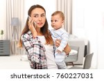 Young Mother Holding Baby Whil...