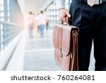 Small photo of Businessman holding a briefcase travellers walking outdoors
