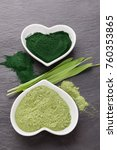 Small photo of Healthy chlorella powder and barley grass from top view. Superfood concept. Wheatgrass. Green nutritional supplement detox.