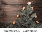 Small photo of Brown wood background. Fir tree fir tree, adorned with slices of mandarin. Christmas greeting card and new year. Xmas and Happy New Year composition. Flat lay, top view