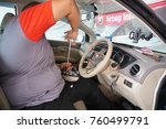 Small photo of Kuala Lumpur, Malaysia - November 2017: A car mechanic replacing the airbag sensor on Nissan Grand Livina car. Nissan Malaysia has to recall all their models due to suspected malfunction of the airbag system.