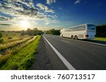 White bus traveling on the asphalt road in a rural landscape at sunset