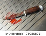 bloody knife with wooden handle on a silver sink top - stock photo