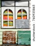 Small photo of Abstract composition with wooden rounded windows, rusty metal plate and colored curtains with sun light in slum area in Thailand, colorful house facade