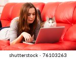 Stock photo young woman lies on the red sofa with cat and working laptop 76103263