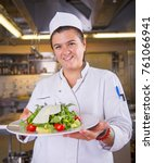 Small photo of Portrait of attractive smiling female chef cook in uniform standing with delicious salat at the kitchen. Female chef holding plate with cooked dish.