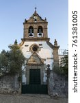 Small photo of Parish church of Sao Romao with a truncated gable showing a rosacea window over the portal, double bells, clock and a cross, in Bacal, Braganca, Portugal