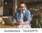 smiling young man using gadgets ... | Shutterstock . vector #761422975