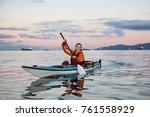 Small photo of Adventurous woman is sea kayaking near Downtown Vancouver, British Columbia, Canada, during a vibrant sunrise. Concept of Adventure and Fitness