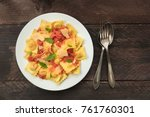 Small photo of An overhead photo of a plate of ravioli with tomato sauce, with grated Parmesan cheese and basil leaves, shot from above on rustic background with a fork, spoon, and a place for text