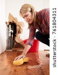 Small photo of Woman mopping up water from a burst pipe with sponge, vertical