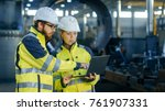 Male and Female Industrial Engineers in Hard Hats Discuss New Project while Using Laptop. They Make Showing Gestures.They Work in a Heavy Industry Manufacturing Factory. - stock photo