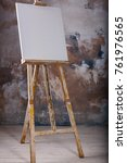 Small photo of White empty artistic canvas on an easel for drawing images by an artist on a gray background