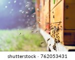 Stock photo close up of flying bees wooden beehive and bees 762053431