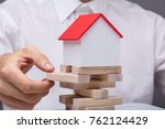 Small photo of Close-up Of Businessman Balancing Property Sector In Business