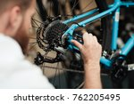 a young guy repairs a bicycle....   Shutterstock . vector #762205495