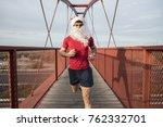 santa claus running on bridge... | Shutterstock . vector #762332701