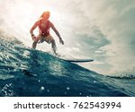 Young Surfer Rides The Ocean...