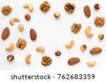 Small photo of Isolated nuts pattern backdrop with copy space. Walnut, cashew, almond and hazelnut on white background. Top view.