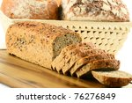 Composition with basket and loafs of bread on breadboard - stock photo