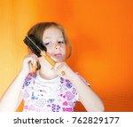 little girl with comb on orange ... | Shutterstock . vector #762829177