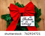 Small photo of A big red Christmas bow over a green Christmas tree branch and Christmas is coming text on a note on wooden table