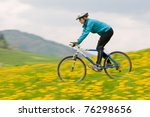 Bike riding - woman downhill on bike in dandelion meadow (intentional motion blur) - stock photo