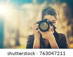 Portrait of a photographer covering her face with the camera. - stock photo