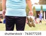 fat man holding football boots...   Shutterstock . vector #763077235