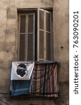 Small photo of Ajaccio, Corsica, 29/08/2017: the Flag of Corsica, a Moor's Head in black wearing a white bandana above his eyes and knotted on the back, adopted in 1755, on a balcony with laundry hanging out to dry