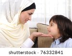 Family of happy Muslim mother and son togethern indoor on couch beside window - stock photo